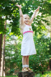 Little blonde girl standing with raised hands  Stock Images
