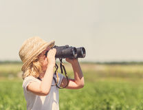 Little blonde girl in straw hat. Looking through binoculars outdoor Royalty Free Stock Images