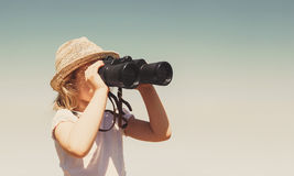 Little blonde girl in straw hat. Looking through binoculars outdoor Stock Images