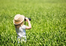 Little blonde girl in straw hat looking through binoculars. Outdoor Stock Photo