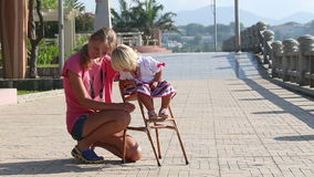 Little blonde girl in Ukrainian national blouse sits on child's chair stock video footage