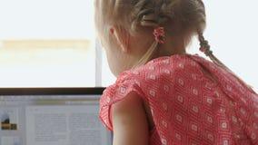 Little blonde girl using laptop stock video