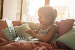 Little girl using her laptop. Stock Photo