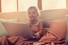 Little girl using her laptop. Little blonde girl using laptop and sitting on couch. Smiling little girl Royalty Free Stock Images