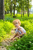 Little blonde girl walking in park Stock Photos
