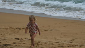 Little blonde girl walking on sandy beach stock video