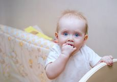 Little blonde girl 1 years old with blue eyes and a round face standing in bed portrait. The child bites his hand. White home inte stock photo