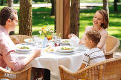 Little blonde-haired son having breakfast with parents. Breakfast with parents. Little blonde-haired son having breakfast with parents while sitting outside Stock Photos