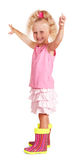 Little blonde with her hands raised in rubber boots isolated. Royalty Free Stock Photography