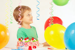 Little blonde kid with birthday cake and balloons Royalty Free Stock Photography