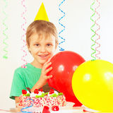 Little blonde kid in holiday cap with birthday cake and balloons Royalty Free Stock Images