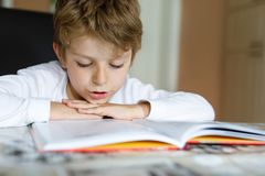 Little blonde school kid boy reading a book at home. Child interested in reading magazine for kids. Leisure for kids stock photography