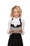 Little blonde student wearing uniform holding tablet Royalty Free Stock Photography