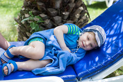 Little blonde toddler boy in swimm suit on couch Stock Image
