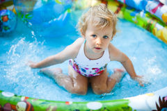 Little blondie girl in swimming pool Royalty Free Stock Image