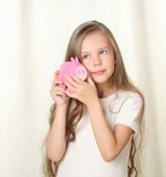 Little blong girl hearing money in piggy moneybox. Little blong girl hearing how much money in piggy moneybox and dreaming about future purchase Royalty Free Stock Images