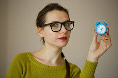 Little blue alarm clock in the hands of an emotional young woman Royalty Free Stock Images