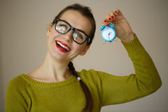 Little blue alarm clock in the hands of an emotional young woman Royalty Free Stock Photography