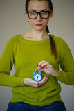Little blue alarm clock in the hands of an emotional young woman Royalty Free Stock Photos