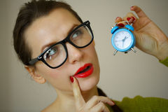 Little blue alarm clock in the hands of an emotional young woman Royalty Free Stock Image