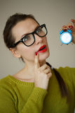 Little blue alarm clock in the hands of pensive young woman. Concept of saving time Stock Photos