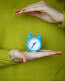 Little blue alarm clock in the hands of pensive young woman. Concept of saving time Stock Image