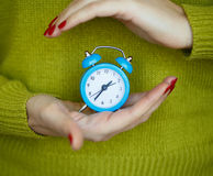 Little blue alarm clock in the hands of pensive young woman. Concept of saving time Royalty Free Stock Photo