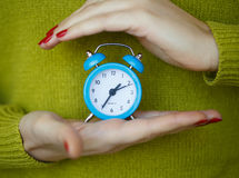 Little blue alarm clock in the hands of women Royalty Free Stock Images