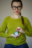 Little blue alarm clock in the hands of young woman Royalty Free Stock Image