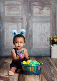 Little Blue Easter Bunny. Adorable baby boy wearing blue bunny ears and playing with a basket of colored plastic eggs.  Room for your text Royalty Free Stock Photo