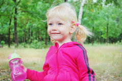 A little blue-eyed blonde girl holding a bottle of water with e Stock Photo