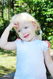 The little blue-eyed blonde . Oh, I did something wrong?. In the summer, in the woods is a little blue-eyed blonde girl with a guilty look, and holds his hand Royalty Free Stock Images