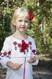 The little blue-eyed blonde standing in embroidery in the woods Stock Image