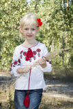 The little blue-eyed blonde standing in embroidery in the woods Royalty Free Stock Images