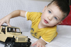 Little blue eyed boy in yellow t-shirt is playing with a big car Stock Photos