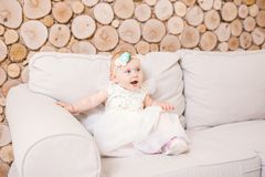 Little blue-eyed girl blond in a white tulle dress with a decoration on her head playing and rejoicing on a beige sofa in a room w Royalty Free Stock Image