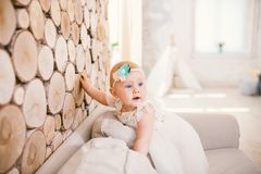 Little blue-eyed girl blond in a white tulle dress with a decoration on her head playing and rejoicing on a beige sofa in a room w Royalty Free Stock Photography