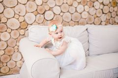 Little blue-eyed girl blond in a white tulle dress with a decoration on her head playing and rejoicing on a beige sofa in a room w Royalty Free Stock Photo