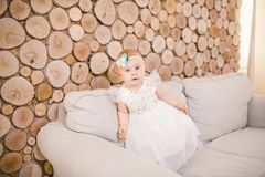 Little blue-eyed girl blond in a white tulle dress with a decoration on her head playing and rejoicing on a beige sofa in a room w Stock Photography