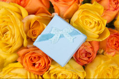Little blue gift box and beautiful bouquet of roses Stock Image