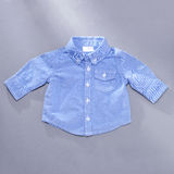 Little blue infant buttoned long sleeve shirt Stock Image