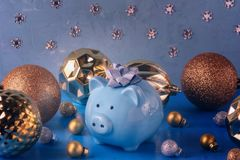 Little blue piggy bank with a bow on his head. Nearby are a lot of gold and silver Christmas balls of various sizes. The. Symbol of the new year. Holiday royalty free stock photos