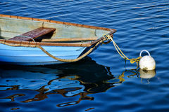 Little Blue Skiff. Small blue boat and reflections at the harbour Stock Image