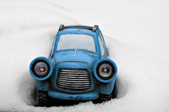 Little Blue toy car stuck in snow. Cute little blue toy car with glowing headlights stuck in snow bank Royalty Free Stock Photography