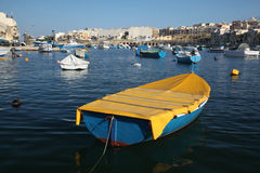 Little boat at Marsascala. A neat yellow and blue dinghy moored in Marsascala's evening light stock photography
