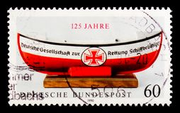Little boat for money-collection, 125th Anniversary of German Lifeboat Institution serie, circa 1990. MOSCOW, RUSSIA - OCTOBER 3, 2017: A stamp printed in Royalty Free Stock Photography