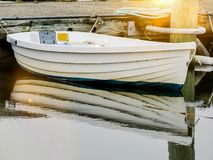 Little boat with sun beam and reflection on water royalty free stock image