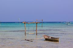 Little boat and swining pole in the water of the pristine coasts of Karimunjawa,Java, Indonesia stock photos