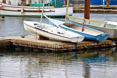 Little Boats Secured On Dock. When not in use the two small sailboats and the rowboat are secured to the top of the floating dock in the harbor Royalty Free Stock Photography