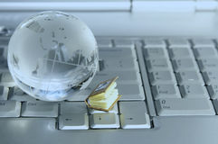 Little book and glass globe on laptop keyboard. Royalty Free Stock Image